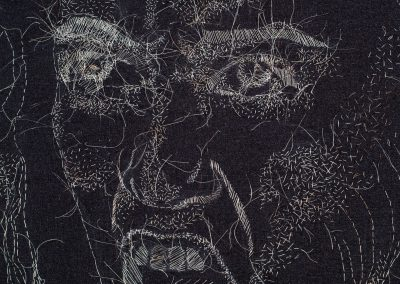Black and gray face drawn/sewn from human hair shown in detail.